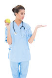 Pretty brown haired nurse in blue scrubs holding a green apple Stock Photo