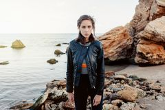 Pretty brunett woman in black leather jacket. Standing near big rock and sea line stock photo