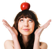 Pretty brunette with an apple on her head. Portrait of a cute brunette with an apple on her head, white background Royalty Free Stock Photo