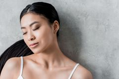 Pretty brunette asian girl with closed eyes. On grey royalty free stock photography