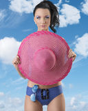 Pretty brunette in bikini with pink hat. Sexy brunette in blue bikini with pink hat and sunglasses, she looks in to the lens and takes the hat on her chest Stock Image