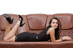 Pretty brunette in black dress laying sofa. Pretty brunette in black dress laying on brown sofa Royalty Free Stock Images