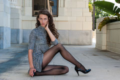 Pretty brunette. In black pantyhose, short dress, and pumps with glimpse of tops with leg crossed over facing right royalty free stock image