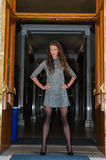 Pretty brunette. In black pantyhose, short dress, and pumps with hands on hips in dark hallway stock image