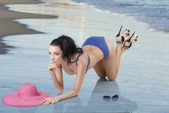 Pretty brunette in blue bikini is kneeling Royalty Free Stock Photo