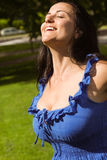 Pretty brunette in blue dress enjoying the sunshine Stock Photo