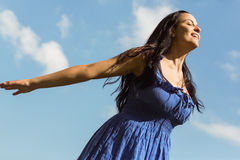 Pretty brunette in blue dress feeling free Royalty Free Stock Image