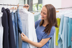 Pretty brunette browsing in the clothes rack Royalty Free Stock Photos