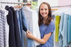 Pretty brunette browsing in the clothes rack Stock Photography