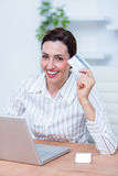 Pretty brunette businesswoman using her credit card Royalty Free Stock Images