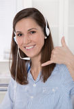 Pretty brunette businesswoman wearing blue blouse with headset Royalty Free Stock Photos