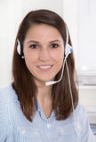 Pretty brunette businesswoman wearing blue blouse with headset Royalty Free Stock Photography