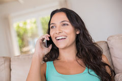 Pretty brunette calling with her mobile phone. At home in the living room Royalty Free Stock Photos
