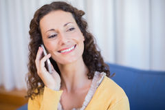 Pretty brunette calling with her mobile phone. In the living room Stock Photography