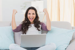 Pretty brunette cheering with laptop Stock Photo
