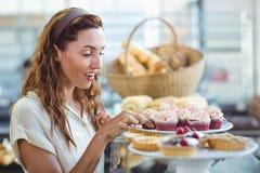 Pretty brunette choosing cupcake Stock Photography