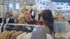 Pretty brunette choosing and trying on a jacket with friend in mall. Professional shot in 4K resolution. 103. You can use it e.g. in your commercial video stock video