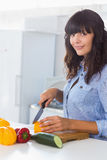 Pretty brunette chopping pepper Stock Photo