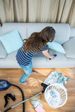 Pretty brunette cleaning the living room Stock Images