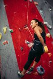 Active happy woman overhanging on tightrope in the training climbing center stock images