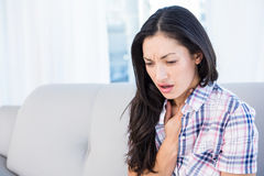 Pretty brunette coughing on couch Stock Photos