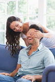 Pretty brunette covering her boyfriends eyes on the couch Royalty Free Stock Image