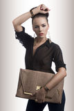 Fashion brunette with bag and hand on the head Stock Photography