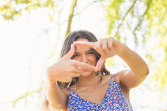 Pretty brunette doing frame with her fingers Stock Photos