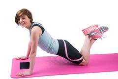 Pretty brunette doing press up on fitness mat Stock Image