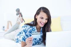Pretty brunette doing shopping online. At home Stock Photo