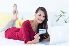 Pretty brunette doing shopping online. At home Royalty Free Stock Images