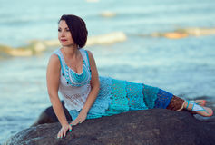 Pretty brunette. Dressed in exquisite handmade sundress, reclines on a rock by the sea Royalty Free Stock Photos