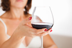Pretty brunette drinking red wine in her bedroom Stock Photos