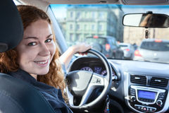 Pretty brunette driving car, looking back at camera Stock Images