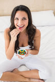 Pretty brunette eating candy in bed Stock Photos