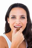 Pretty brunette eating chocolate candy stock photos