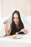 Pretty brunette eating cupcake in bed Stock Photography