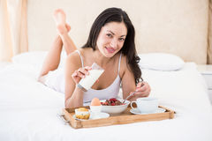 Pretty brunette eating her breakfast on bed Royalty Free Stock Photo