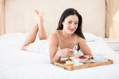 Pretty brunette eating her breakfast on bed Royalty Free Stock Photography