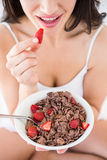 Pretty brunette eating strawberries on bed Stock Photography