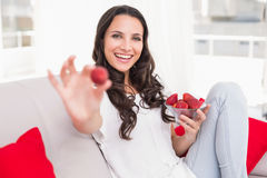 Pretty brunette eating strawberries on couch Royalty Free Stock Images