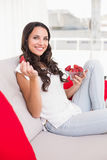 Pretty brunette eating strawberries on couch Royalty Free Stock Photos