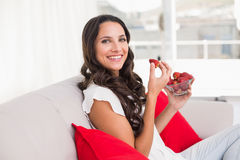 Pretty brunette eating strawberries on couch Royalty Free Stock Photography