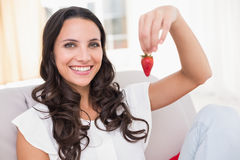 Pretty brunette eating strawberries on couch Stock Images