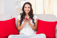 Pretty brunette eating strawberries on couch Royalty Free Stock Image