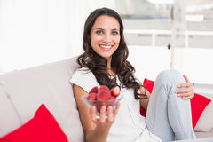 Pretty brunette eating strawberries on couch Stock Photo