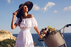 Pretty brunette in elegant dress and hat riding a bicycle along the coast Stock Photos