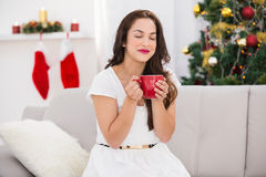 Pretty brunette enjoying a hot drink at christmas Royalty Free Stock Photos
