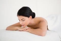 Pretty brunette enjoying a massage at camera Stock Images