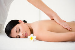 Pretty brunette enjoying a massage with flower Royalty Free Stock Photography